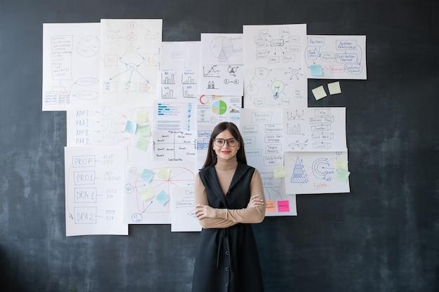 Giovane economista femminile elegante in piedi dalla lavagna con diagrammi di flusso e diagrammi sui documenti