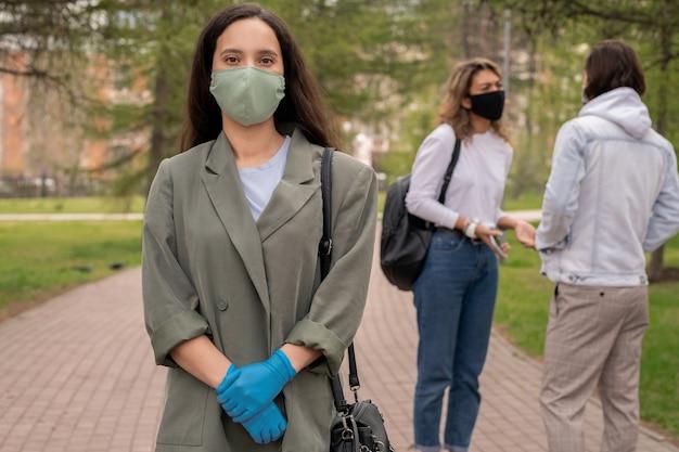 Giovane donna elegante in giacca lunga e maschera protettiva e guanti in piedi nel parco pubblico