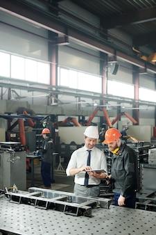 Giovane caposquadra elegante e il suo subordinato in abiti da lavoro discutendo disegno tecnico nel touchpad alla riunione nell'officina della fabbrica