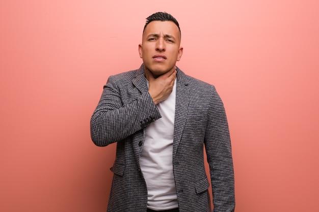 Giovane uomo latino elegante che tossisce, malato a causa di un virus o di un'infezione