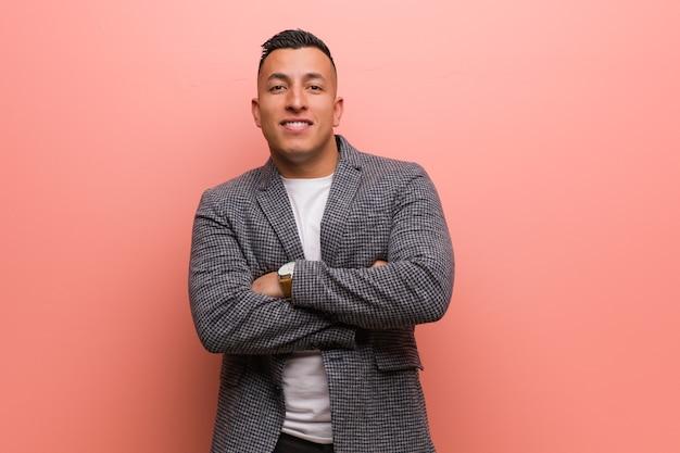 Giovane uomo latino elegante che attraversa le braccia, sorridente e rilassato