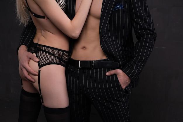 Un giovane uomo elegante abbraccia appassionatamente una ragazza bionda in mutande