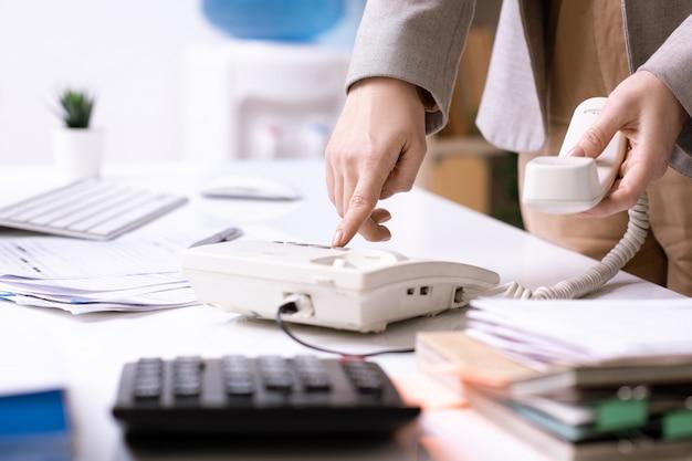 Elegante giovane manager di ufficio o imprenditrice premendo il pulsante del telefono durante la composizione del numero per chiamare uno dei clienti