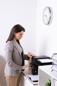 Elegante giovane manager di ufficio premendo il pulsante di avvio sul pannello della macchina xerox durante la copia del documento finanziario