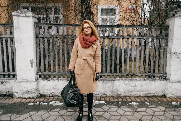 Giovane ragazza bionda elegante elegante con gli occhiali e borsa da viaggio in posa sopra il vecchio recinto sulla strada