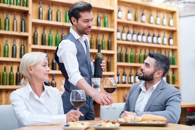 Giovane cameriere o barista elegante che consiglia ai suoi clienti un nuovo tipo di vino rosso dopo il pranzo in ristorante