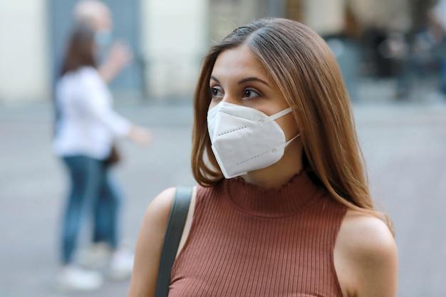 Giovane donna elegante in via della città che indossa la maschera protettiva kn95 ffp2