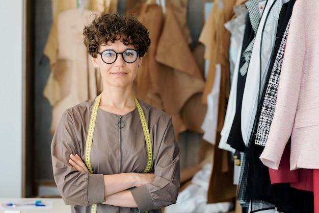 Giovane donna elegante in occhiali ti guarda mentre si trova nel suo studio di moda o boutique