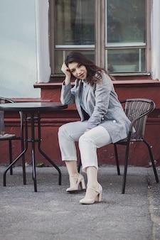 Giovane donna elegante in giacca e occhiali seduti in street cafe
