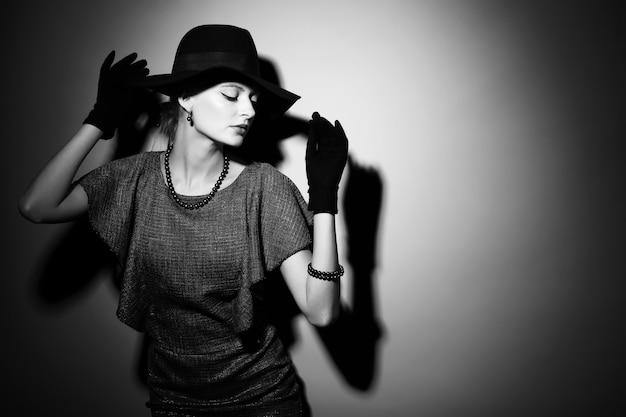Giovane donna elegante, moda retrò, cappello, guanti, vestito. immagine in bianco e nero.