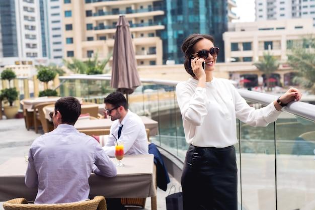 Giovane donna elegante in camicia e gonna parlando al telefono.