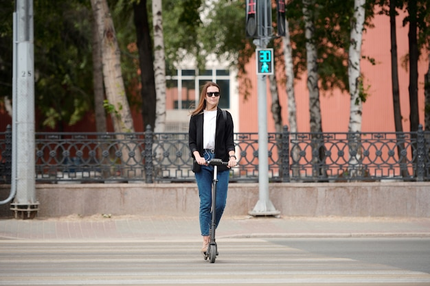 Giovane donna elegante con occhiali da sole e abbigliamento casual in piedi su uno scooter elettrico e che si muove lungo le strisce pedonali mentre le luci verdi sono accese