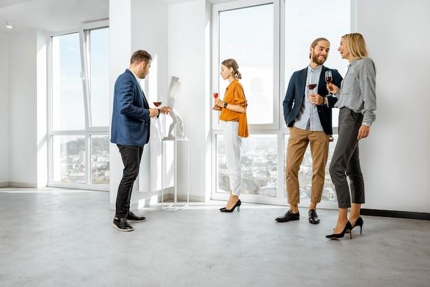 Giovani vestiti elegantemente che si incontrano nel corridoio bianco o nello showroom del museo d'arte moderna, bevendo vino e guardando la scultura