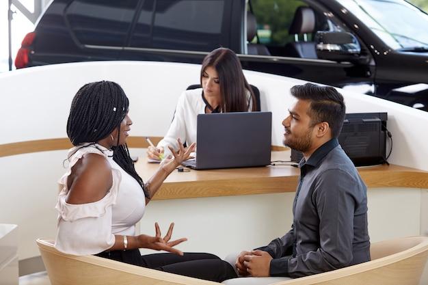 Una giovane coppia afroamericana emotiva comunica sullo sfondo di un agente di vendita di auto
