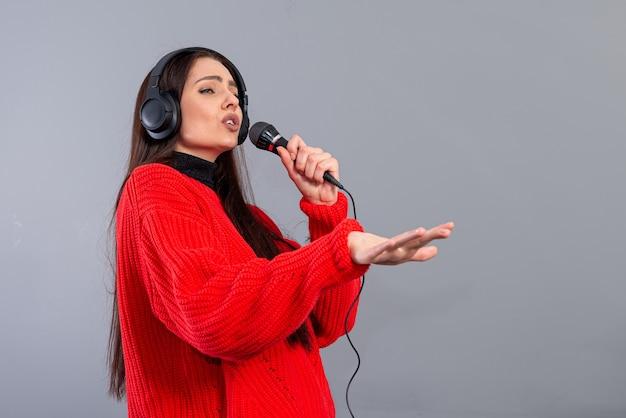Giovane, bruna emotiva con le cuffie e un microfono vestito con un maglione rosso canta il karaoke, isolato su grigio