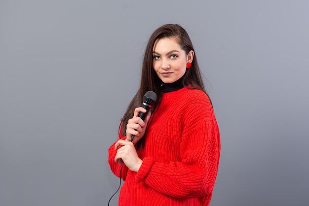Giovane, bruna emotiva con un microfono vestito con un maglione rosso canta il karaoke o dice un discorso, isolato su grigio