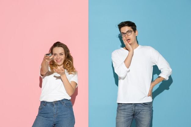 Giovane uomo e donna emotivi su sfondo rosa e blu