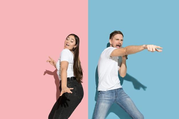 Giovane uomo emotivo e donna sulla parete rosa e blu