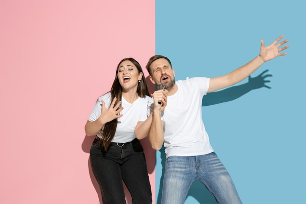 Giovane uomo e donna emotivi sul muro rosa e blu