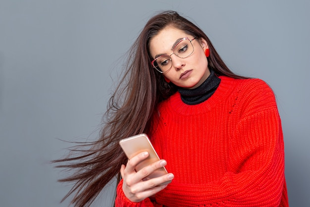 Giovane femmina adolescente emotiva con gli occhiali vestita con un maglione rosso in posa su un muro grigio