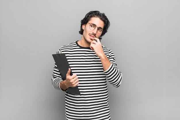 Uomo giovane impiegato che tiene un inventario rilassato pensando a qualcosa guardando uno spazio di copia.