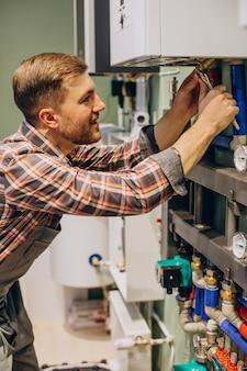 Giovane ingegnere che regola il riscaldamento autonomo