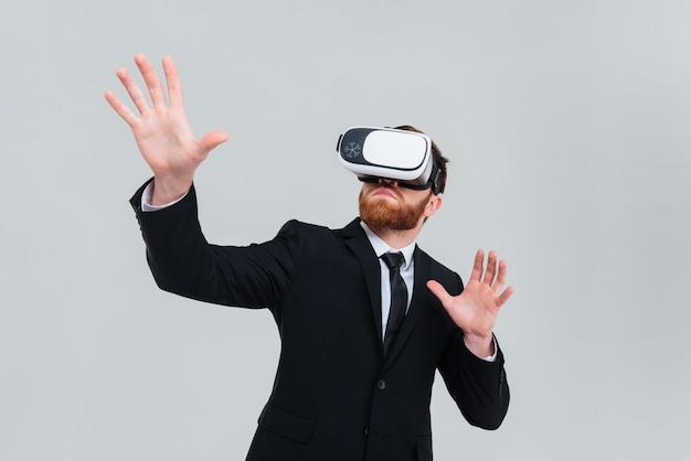 Giovane ingegnere in abito nero che indossa un dispositivo di realtà virtuale. sfondo grigio isolato