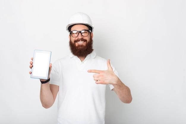 Il giovane ingegnere vestito in uniforme bianca sta indicando il suo tablet.
