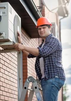 Giovane ingegnere che installa il condizionatore d'aria sulla parete esterna dell'edificio