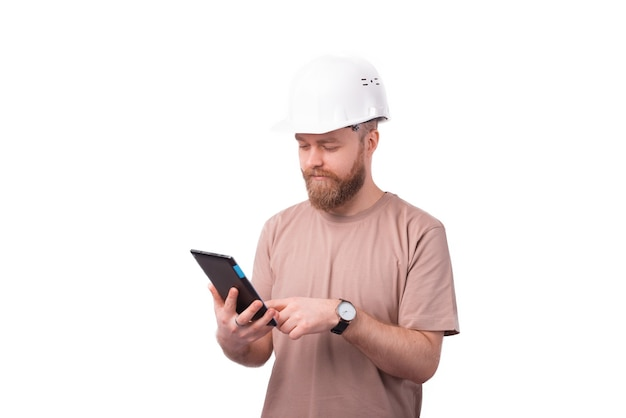 Giovane ingegnere uomo utilizzando tablet e indossando elmetto protettivo su bianco