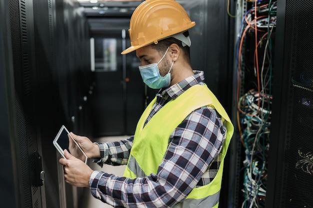 Giovane ingegnere uomo che lavora all'interno della stanza del centro dati mentre indossa la maschera di sicurezza - focus sulla faccia dell'uomo