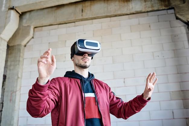Giovane ingegnere con occhiali vr in piedi davanti al display virtuale e toccandolo mentre guarda esempi di costruzioni costruite