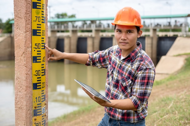 Giovane ingegnere che lavora sul posto presso la diga