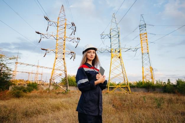 Un giovane ingegnere ispeziona e controlla le apparecchiature della linea elettrica. energia.