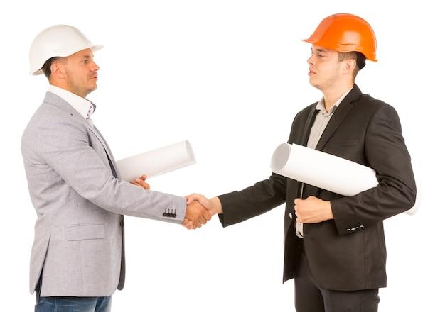 Giovani ingegneri che si stringono la mano tenendo i progetti