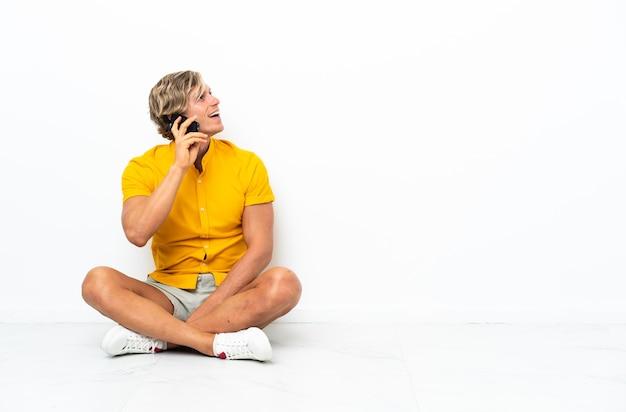 Giovane uomo inglese seduto sul pavimento mantenendo una conversazione con il telefono cellulare