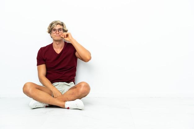 Giovane uomo inglese seduto sul pavimento che mostra un segno di gesto di silenzio
