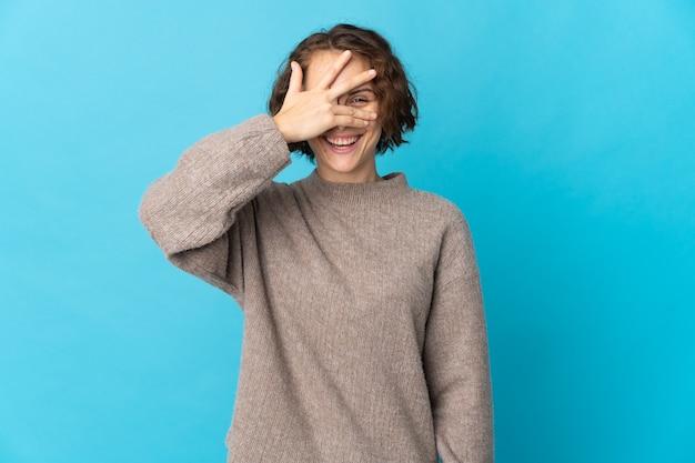 Giovane donna inglese su occhi blu che coprono con le mani e sorridente