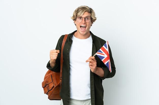 Giovane donna inglese che tiene una bandiera del regno unito che celebra una vittoria nella posizione del vincitore