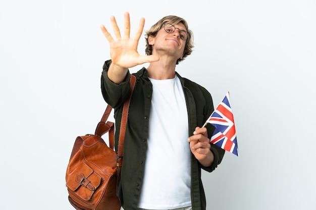 Giovane donna inglese che tiene una bandiera del regno unito che conta cinque con le dita