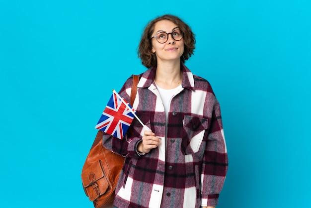 Giovane donna inglese che tiene una bandiera del regno unito isolata sulla parete blu e che osserva in su