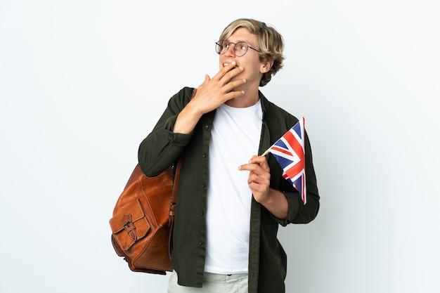 Giovane donna inglese che tiene una bandiera del regno unito che osserva in su mentre sorride