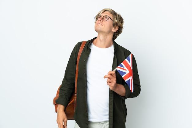 Giovane donna inglese che tiene in mano una bandiera del regno unito e guarda in alto
