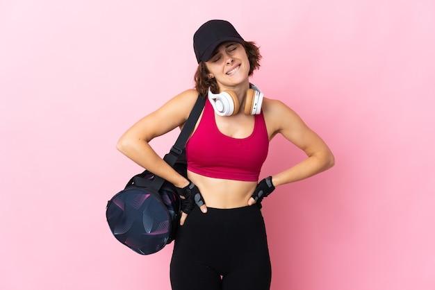 Giovane donna inglese isolata su sfondo rosa che soffre di mal di schiena per aver fatto uno sforzo