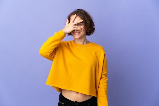 Giovane donna inglese isolata sulla parete viola che copre gli occhi con le mani e sorridente
