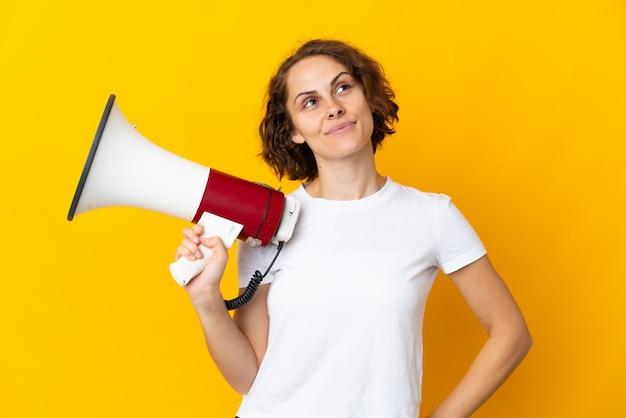 Giovane donna inglese isolata sulla parete gialla che tiene un megafono e che pensa