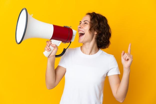 Giovane donna inglese isolata sulla parete gialla che grida tramite un megafono per annunciare qualcosa in posizione laterale