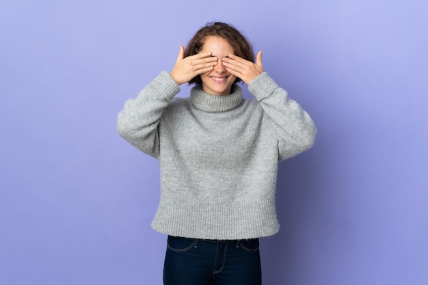 Giovane donna inglese su sfondo viola che copre gli occhi con le mani e sorridente