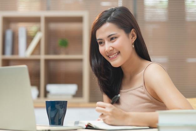 Giovane imprenditore asiatico donna d'affari che lavora in ufficio a casa con internet utilizzando il computer