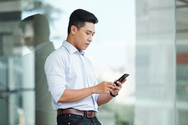 Giovane imprenditore che controlla il telefono